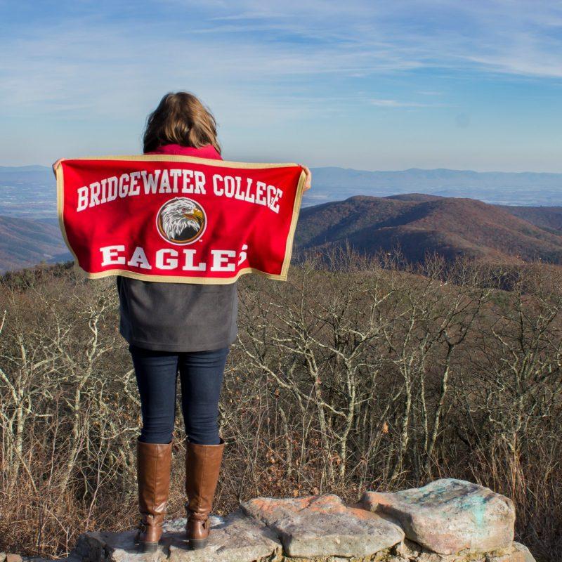 Student at Reddish Knob holding Bridgewater College flag
