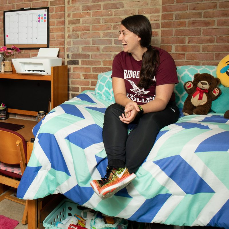 Two female students sitting on beds in a dorm room