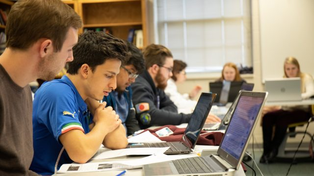 Students study in class behind laptops