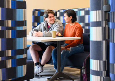 Two students sitting at a table in a blue colored booth||Two students sitting at a table in a blue colored booth