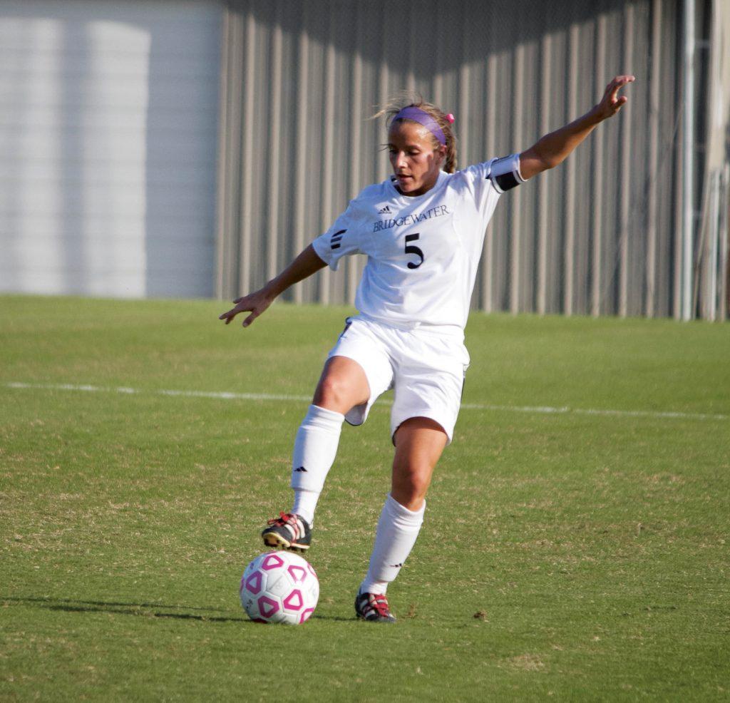Young woman kicks a soccer ball on a field