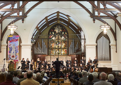 Photo of orchestra performing in a church||Photo of orchestra performing in a church