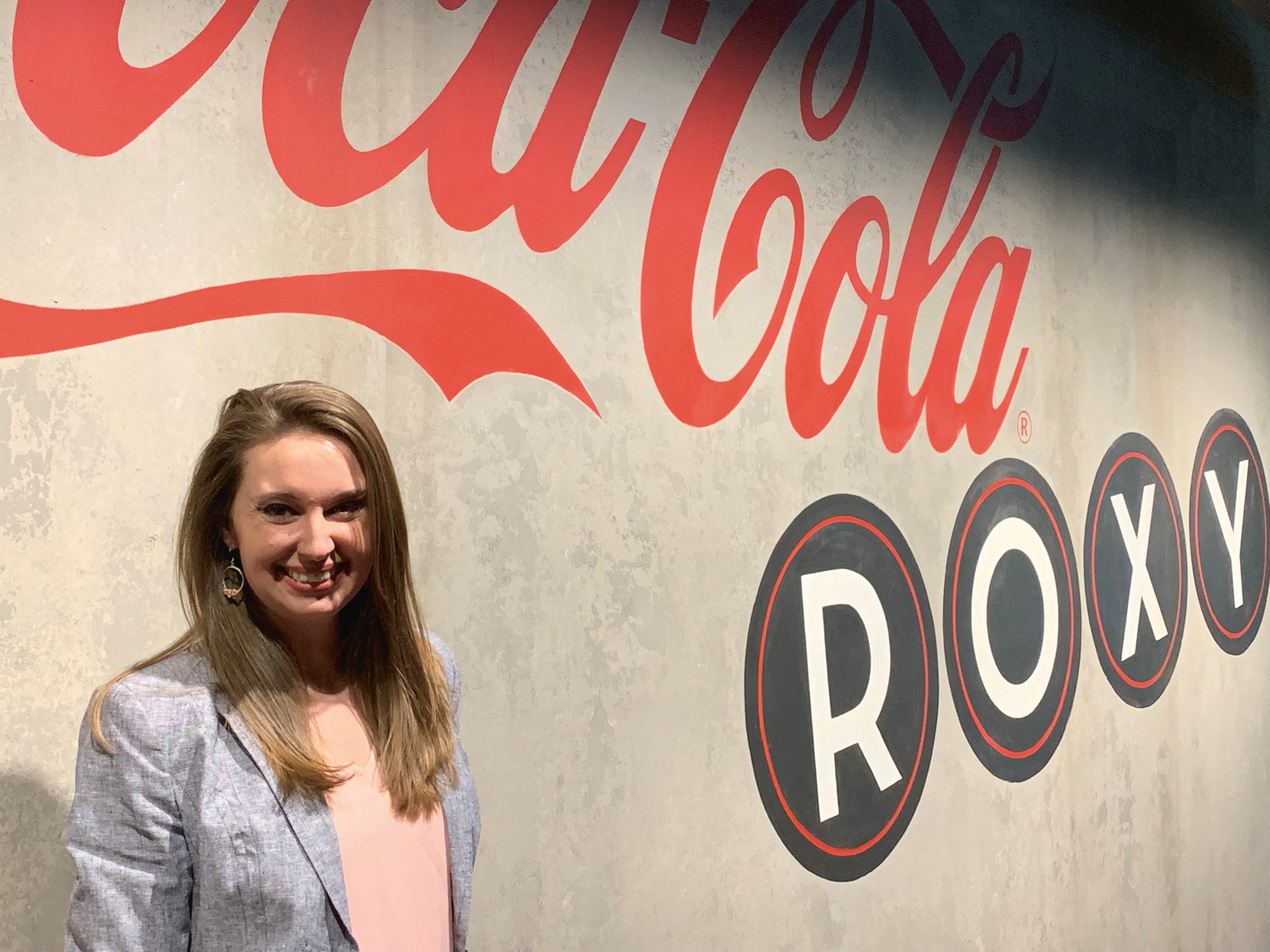 Young man stands next to a wall that says Coca-Cola Roxy