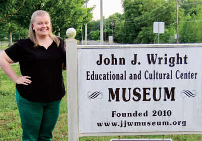 Woman stands next to a sign that reads John J. Wright Educational and Cultural Center Museum Founded 2010 www.jjwmuseum.org|Woman stands next to a sign that reads John J. Wright Educational and Cultural Center Museum Founded 2010 www.jjwmuseum.org