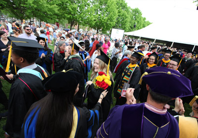 young woman holding flowers wearing a cap and gown in a crows of people                