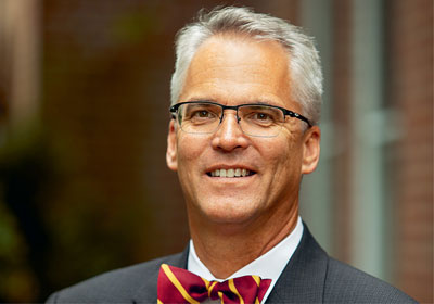 Man in bowtie and glasses smiles at camera