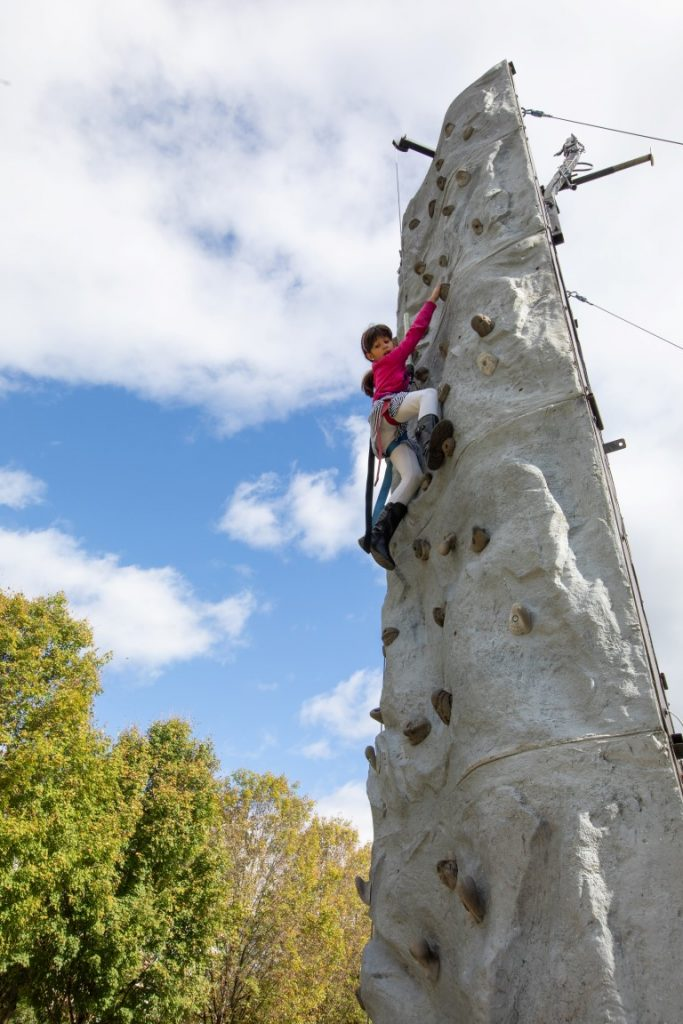A young girl climbs up a rock wall