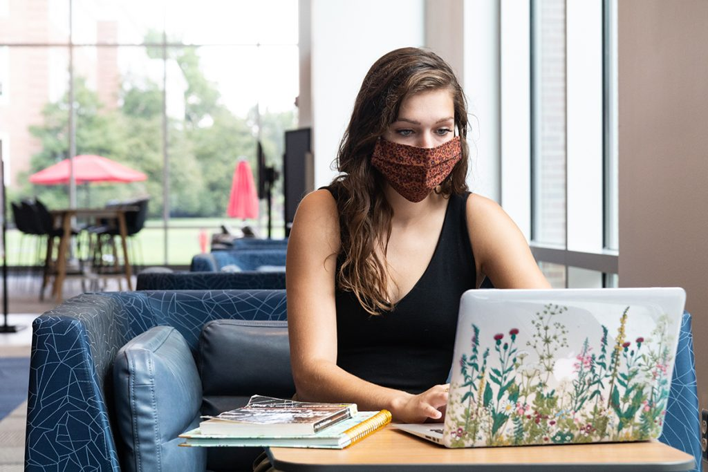 Young lady wearing a mask sits in front of a laptop